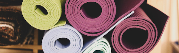 A group of yoga mats rolled up.